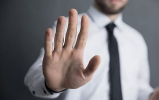 """businessman with hand raised in """"stop"""" position"""